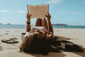 Lenses for sunglasses - lady on the beach lying on the sand and reading her book