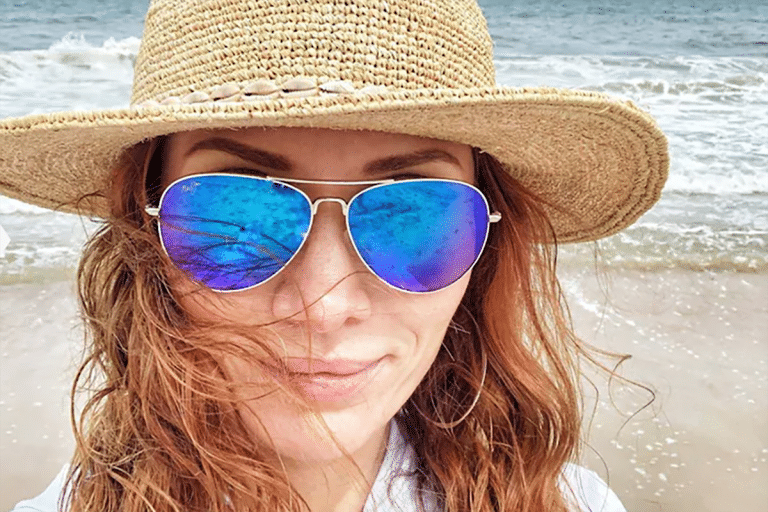 Sports sunglasses - woman on beach wearing blue tint sunglasses