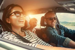 Lenses for sunglasses - a couple and their children laughing as they drive in the bright sunshine