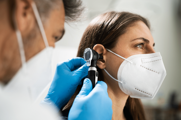 Hearing loss and ear health conditions: Audiologist looking into patient's ear with otoscope