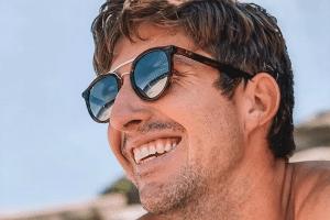 Sunglasses - man smiling on a beach wearing sports sunglasses