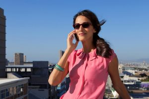 Lenses for glasses - Woman on phone in the sun with full tint in glasses