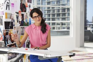 Lenses for glasses - Woman working indoors at her desk with glasses on