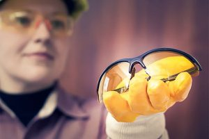 Prescription safety glasses -Woman holding a pair of prescription safety glasses