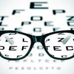 Book an eye test - eyeglasses over a blurry eye chart